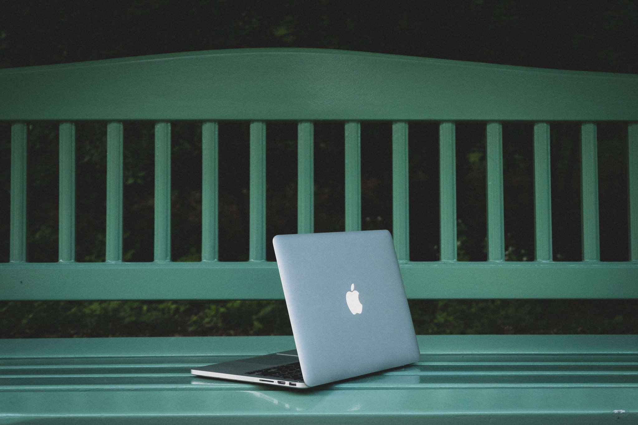 laptop in a green bench